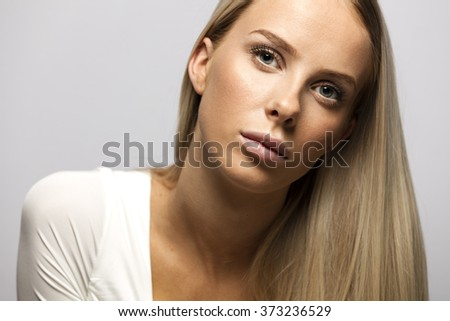 Portrait of a casual blonde woman in white top - stock photo