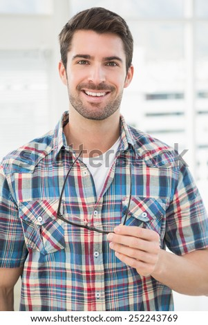 Portrait of a casual businessman holding his glasses in the office - stock photo