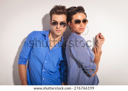 Portrait of a casual couple posing against a grey wall. - stock photo