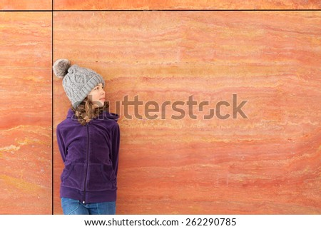 portrait of a casual little girl with wool hat, outdoors - stock photo