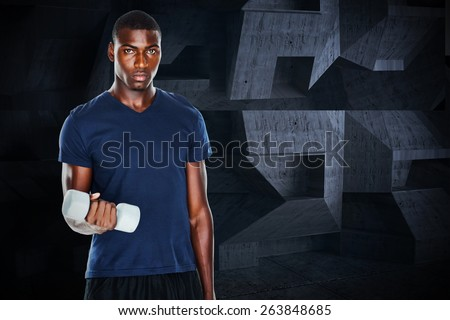 Portrait of a casual man lifting dumbbells against dark room