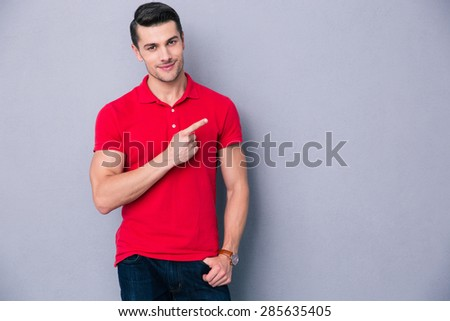Portrait of a casual man pointing away over gray background - stock photo