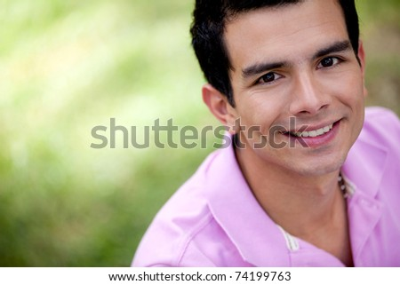 Portrait of a casual man smiling outdoors - stock photo
