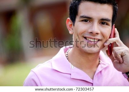 Portrait of a casual man talking on the phone outdoors - stock photo