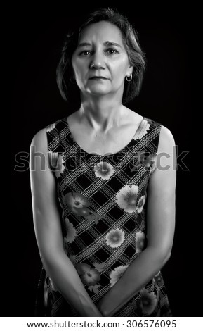 Portrait of a casual middle aged woman isolated over black background. Black & White picture. - stock photo