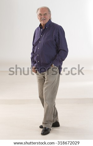 Portrait of a casual senior businessman smiling in his office - stock photo