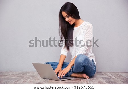 Portrait of a casual woman sitting on the floor with laptop on gray background - stock photo