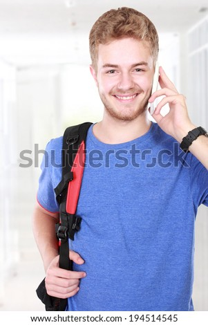 Portrait of a casual young man speaking on the phone and smiling to the camera - stock photo