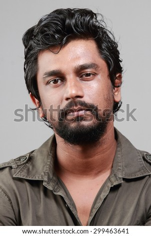 Portrait of a casually dressed Indian young man with beard. - stock photo