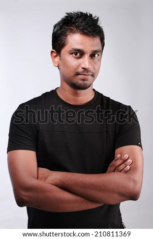 Portrait of a casually dressed  Indian young man with folded hands - stock photo