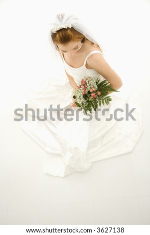 Portrait of a Caucasian bride holding bouquet.