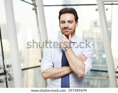 portrait of a caucasian business executive standing by the window in office, hand on chin. - stock photo