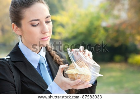 Portrait of a caucasian businesswoman eating donut princess, outdoor - stock photo
