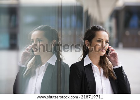 Portrait of a Caucasian businesswoman standing outside using mobile phone - stock photo