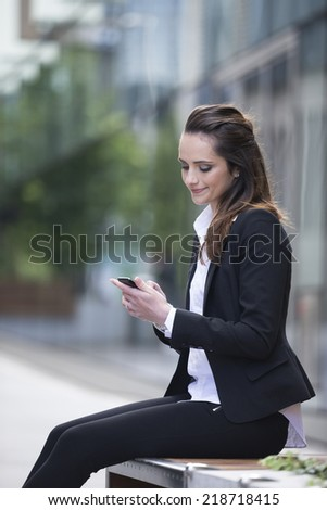 Portrait of a Caucasian businesswoman standing outside using mobile phone to send a message.