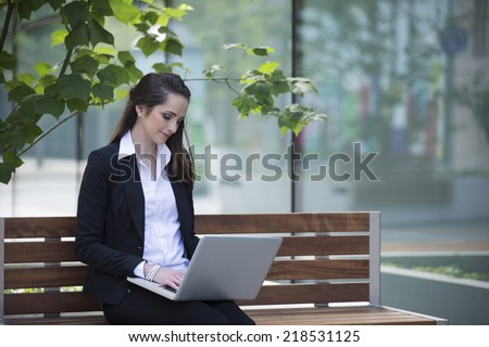 Portrait of a Caucasian businesswoman using a laptop outdoors. - stock photo