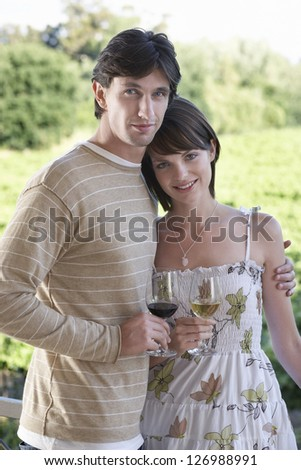 Portrait of a caucasian couple standing with a glass of wine