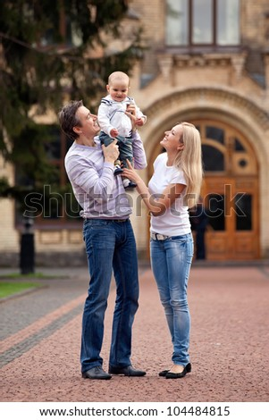 Portrait of a Caucasian couple with one-year old boy outdoors - stock photo