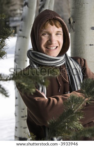 Portrait of a Caucasian male teenager wearing hoodie and scarf in winter setting. - stock photo