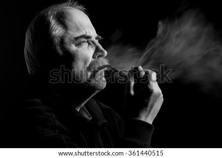 Portrait of a caucasian man smoking tobacco pipe - stock photo