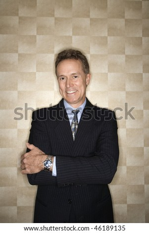 Portrait of a Caucasian middle-aged businessman wearing a suit and smiling at the camera. Vertical format. - stock photo