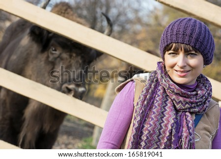 Portrait of a caucasian woman with the European bison (Bison bonasus) behind the fence. - stock photo