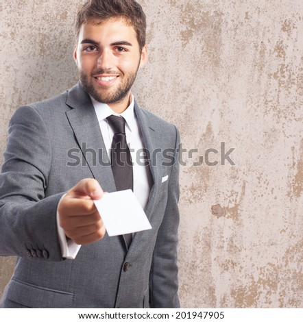 portrait of a caucasian young business man giving a personal card - stock photo