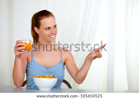 Portrait of a caucasian young woman eating healthy breakfast and pointing to the right - stock photo