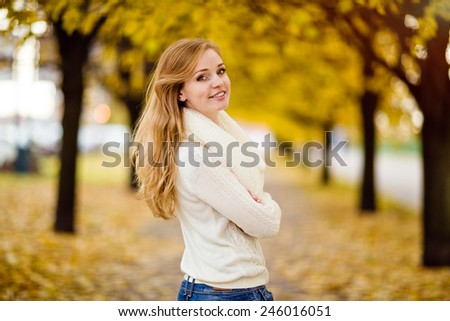 portrait of a charming and smiling redhead girl with freckles on the autumn landscape - stock photo