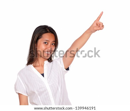 Portrait of a charming asiatic young woman looking at you while is pointing to left up against white background - copyspace