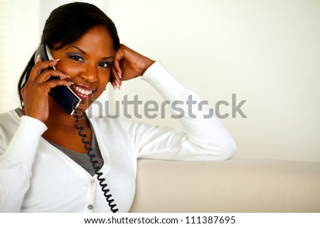 Portrait of a charming black woman looking and smiling at you while speaking on phone. With copyspace