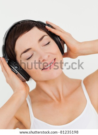 Portrait of a charming brunette listening to music against a white background