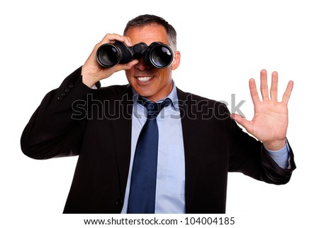 Portrait of a charming business man looking forward through binoculars and greeting on black suit against white background - stock photo