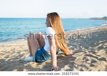 Portrait of a charming dreamy woman enjoying beautiful sea landscape while sitting alone on the beach in summer day, attractive young thoughtful hipster girl relaxing after promenade during weekend - stock photo