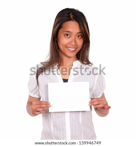 Portrait of a charming ethnic young woman holding a white card with copyspace while is looking at you on isolated background