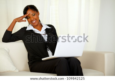 Portrait of a charming executive black woman reading on laptop screen. Sitting on a couch and laughing and having fun while working at home - stock photo