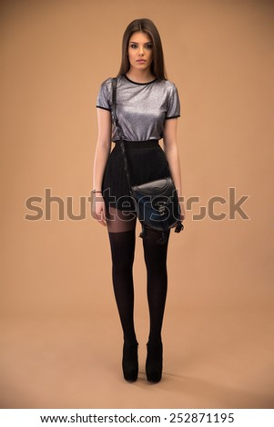 Portrait of a charming fashion woman over brown background - stock photo