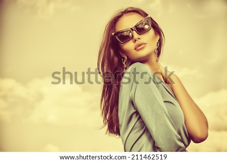 Portrait of a charming lady in beautiful elegant dress and sunglasses against the sky. - stock photo