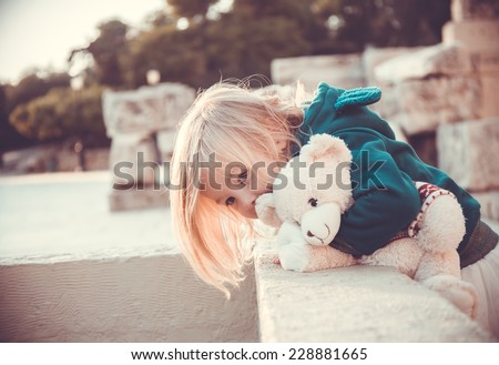 Portrait of a charming little girl wearing green hoodie and hugging Teddy bear looking downstairs on sunset - stock photo