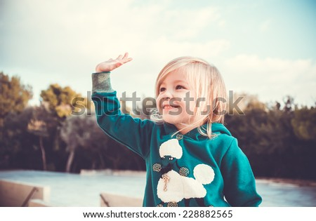 Portrait of a charming little girl wearing green smock waiving her arm - stock photo