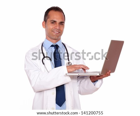 Portrait of a charming medical doctor working on his laptop computer while is looking at you on isolated background