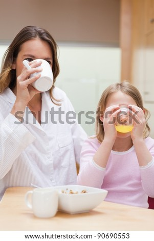 Portrait of a charming mother and her daughter having breakfast in a kitchen - stock photo