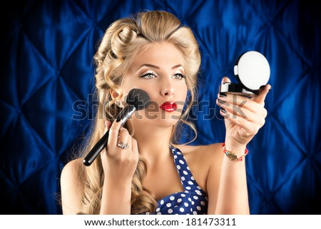 Portrait of a charming pin-up girl doing makeup in front of a mirror. - stock photo