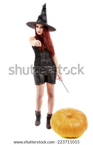 portrait of a charming red-haired witch holding pumpkin . Halloween. Isolated over white.