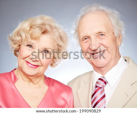Portrait of a charming retired couple looking at camera in isolation - stock photo