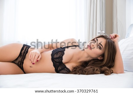 Portrait of a charming sexy woman in lingerie lying on the bed and looking at camera - stock photo