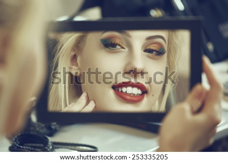 Portrait of a charming smiling woman admiring herself in the mirror. Beauty makeup, skin care and cosmetics treatment. Shallow depth of field and mate color grading. - stock photo