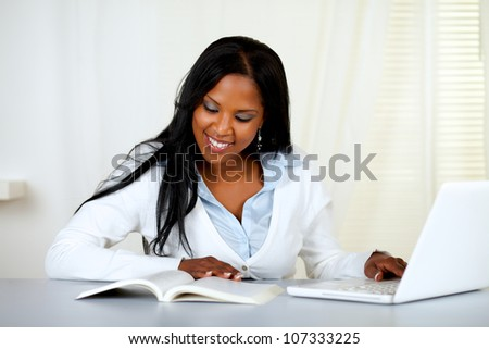 Portrait of a charming student woman browsing a book at home - stock photo