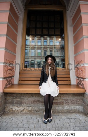 Portrait of a charming woman dressed in classy stylish clothes sitting on a wooden bench on the street, young female tourist with trendy look resting after walking in the city during her amazing trip - stock photo