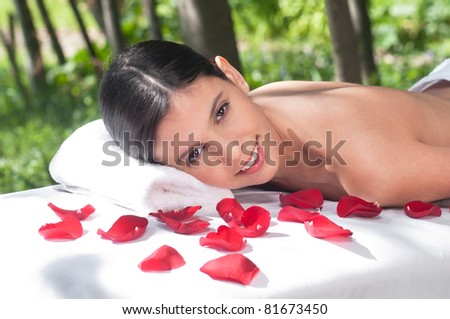 Portrait of a charming woman lying on a massage table in a health spa - stock photo